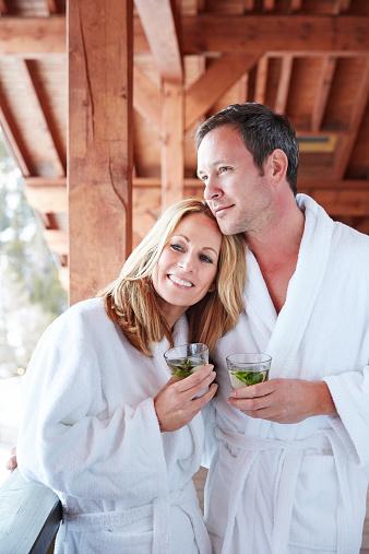 Couple in bathrobes hugging on balcony